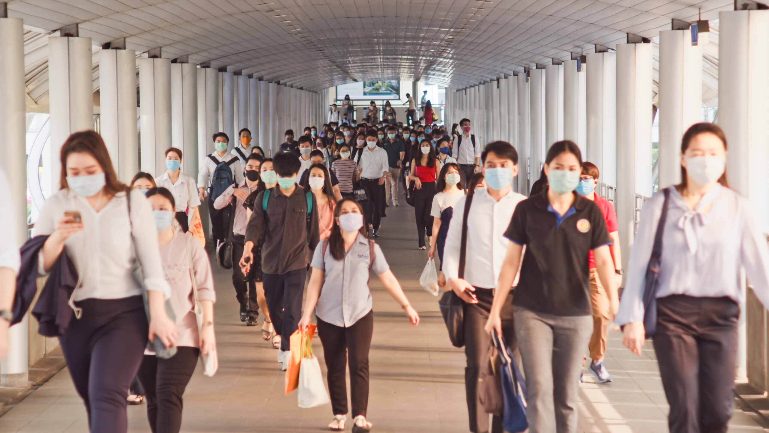 asiand leaving a train station and wearing masks